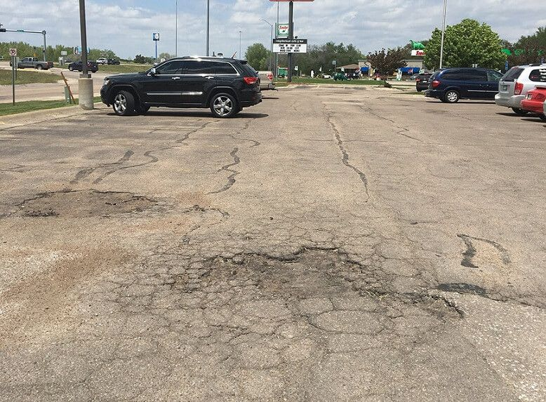 potholes and cracked pavement in applebees parking lot