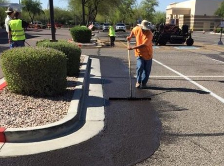 worker seal coating parking lot