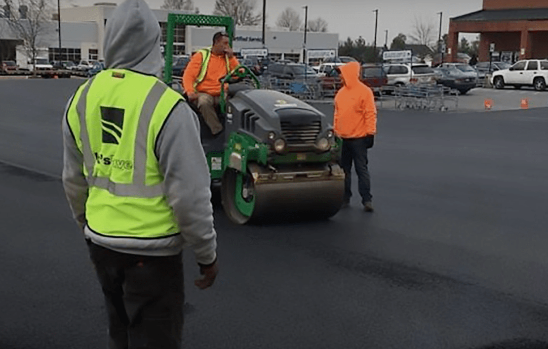 let's pave contractors working on pavement parking lot