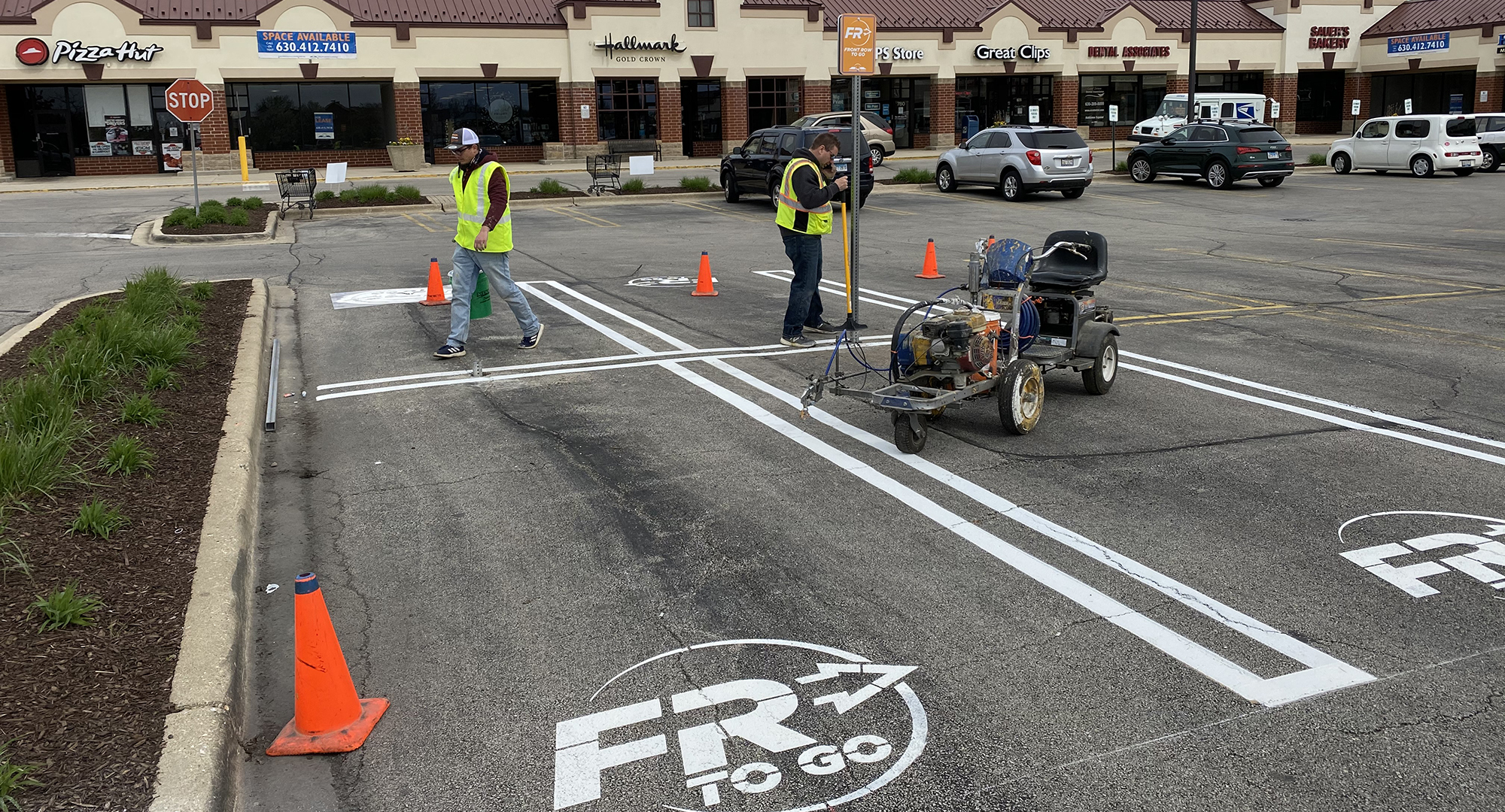 two gentleman painting the lines in the parking lot for curbside parking