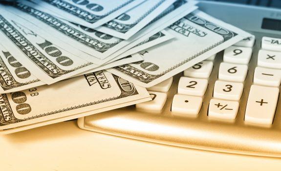 cash laying on calculator