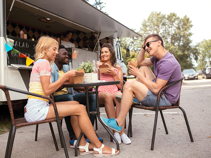 group of friends sitting at table in front of food truck