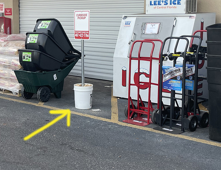 curbside parking sign inside of bucket with arrow pointing to it